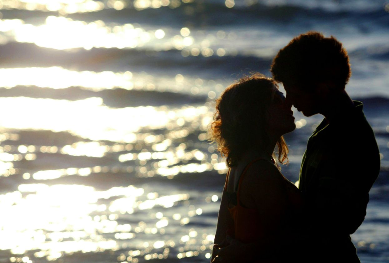 Couple kissing in front of the ocean.