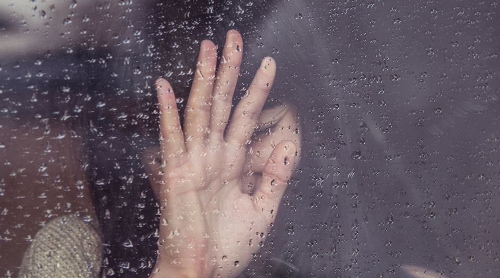 girl crying against a window