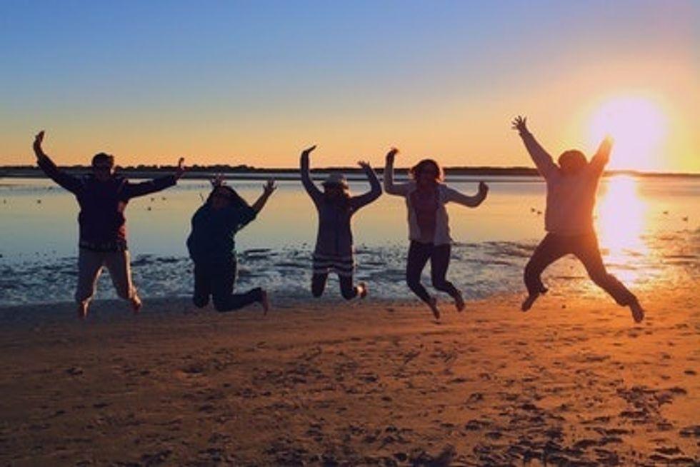 People Jumping On Beach