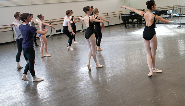 A group of ballet students practices a combination by following the instructor