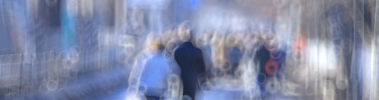 A fuzzy image of people walking in a city, representative of non-sharp memory recall.