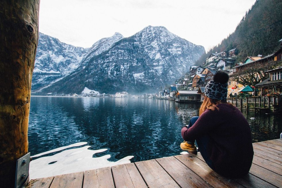 https://www.pexels.com/photo/woman-in-purple-sweater-sitting-on-wooden-floor-with-view-of-lake-and-mountains-789382/