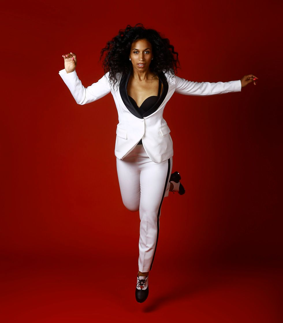 Chloe Arnold is tap dancing in front of a red background. She is wearing a white suit and hopping with one leg in the air.