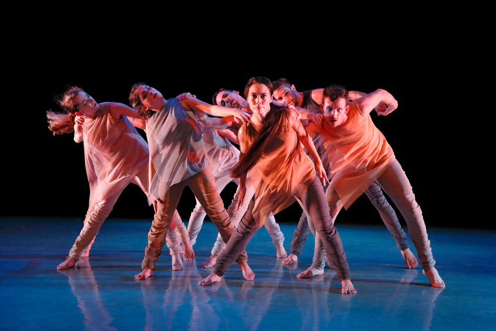 A groups of dancers grab each other's shoulders and all lean to the same side