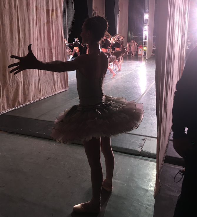 Tricia Albertson stretches her arms to the sides backstage in the wings