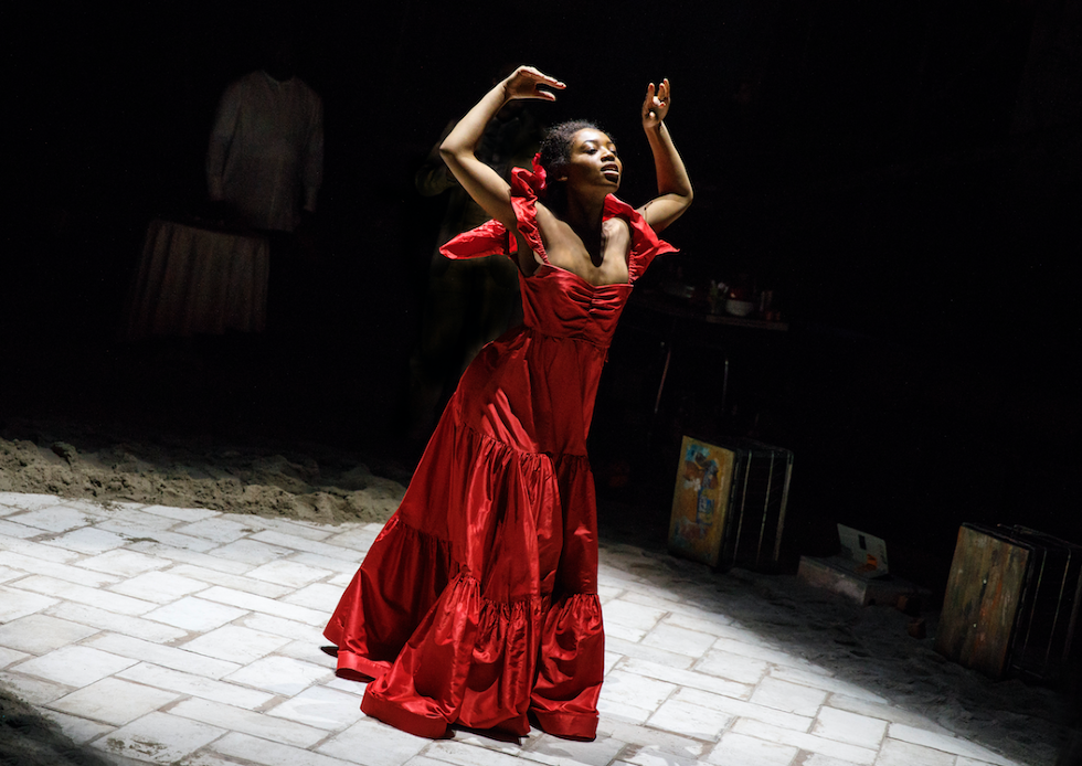 An actress in a red dress leans forward onstage, her hands above her head
