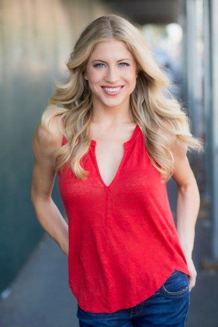 A head shot of the performer. She has long blond hair and is wearing a red shirt.