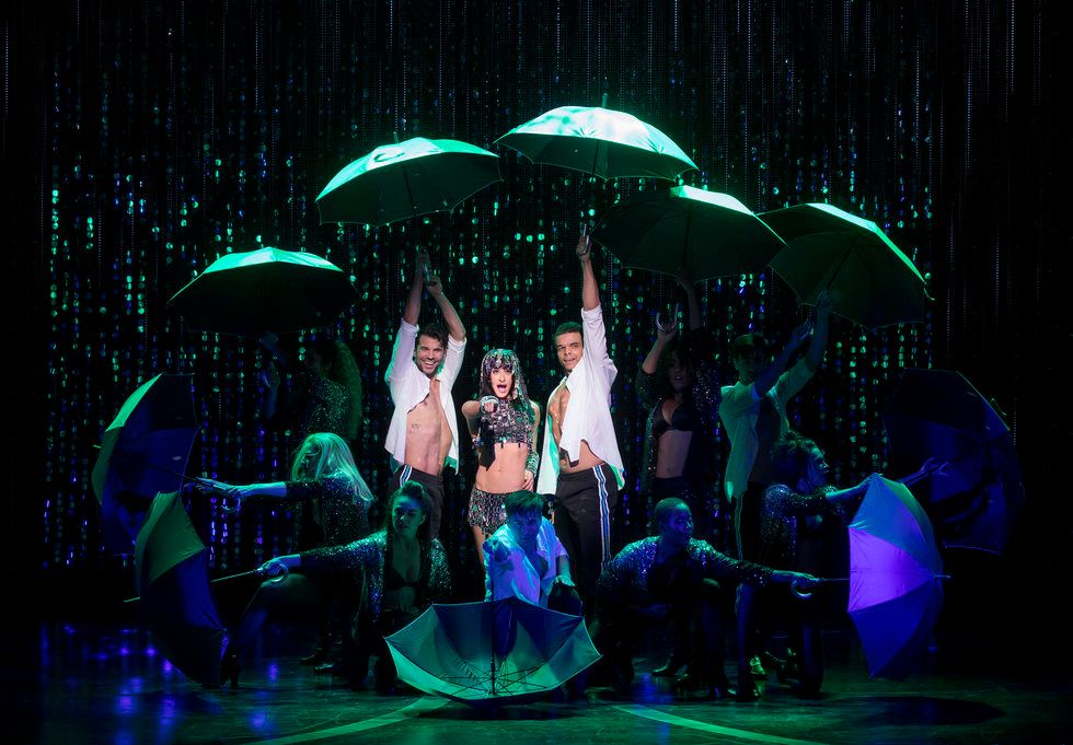 A photo from The Cher Show. Cher is pointing toward the audience and wearing a silver, sparkly costume. She is surrounded by dancers holding open umbrellas.