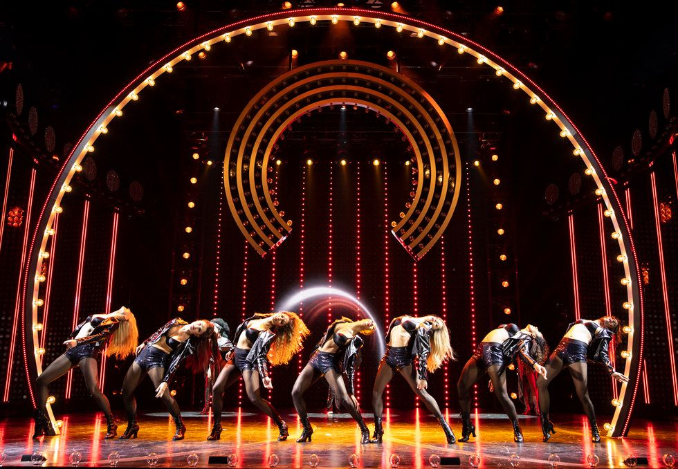 A line of female dancers arch backwards. Their hair is down and they're wearing black boots, tights, a bra and jacket.