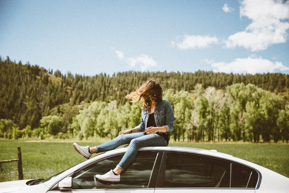 woman in jeans and denim jacket sitting on top of white car on sunny day