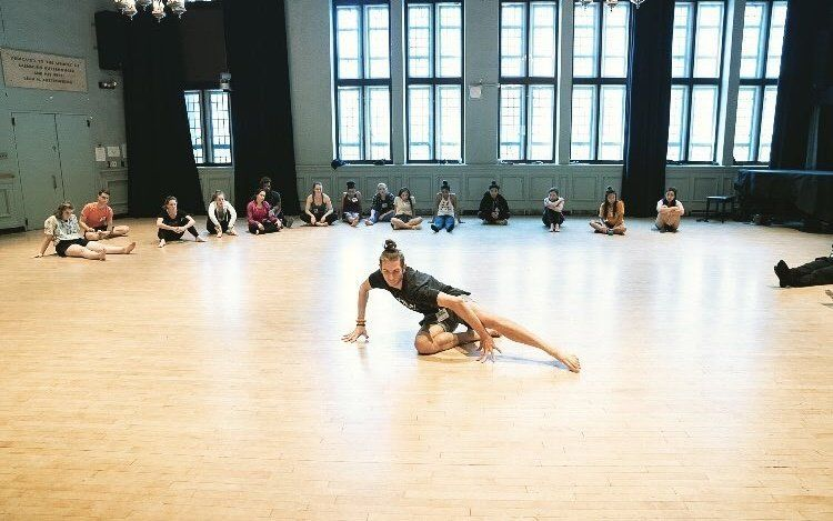 Dancer Isaac Iskra dances in a classroom, while the other students watch