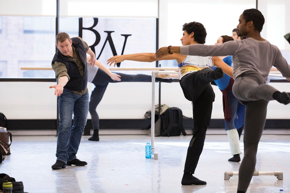 Skulte coaches two male dancers during battements at the barre.
