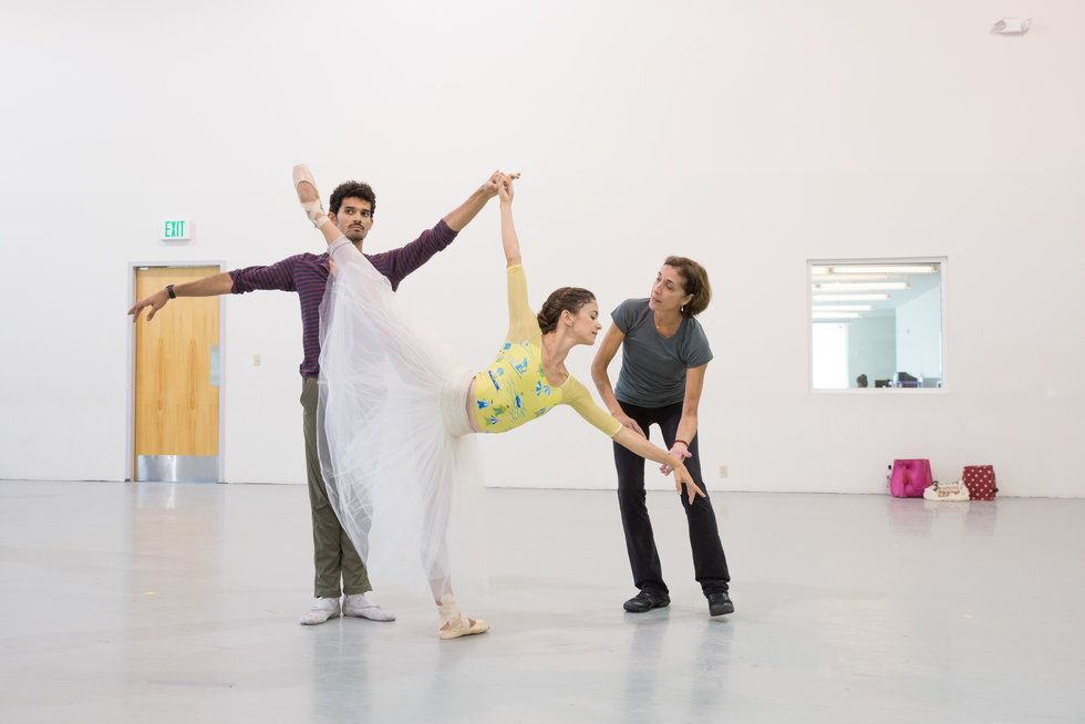 A ballet rehearsal with a female dancer in pench\u00e9. A male partner is holding her hand, while the artistic director coaches her.