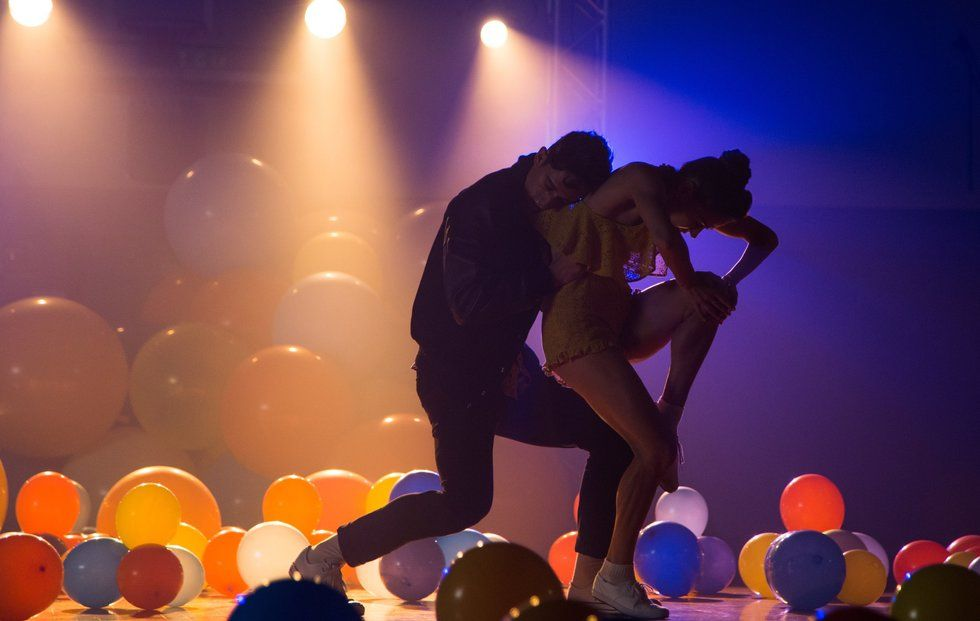 Two dancers embracing in an empty gym full of balloons.