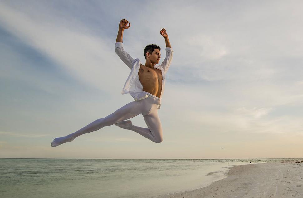 Xavier Nunez leaps on the beach at sunset
