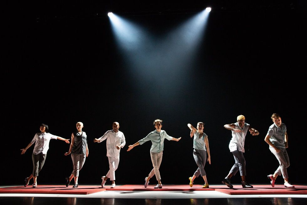 a lineup of tap dancers across the stage, in lights