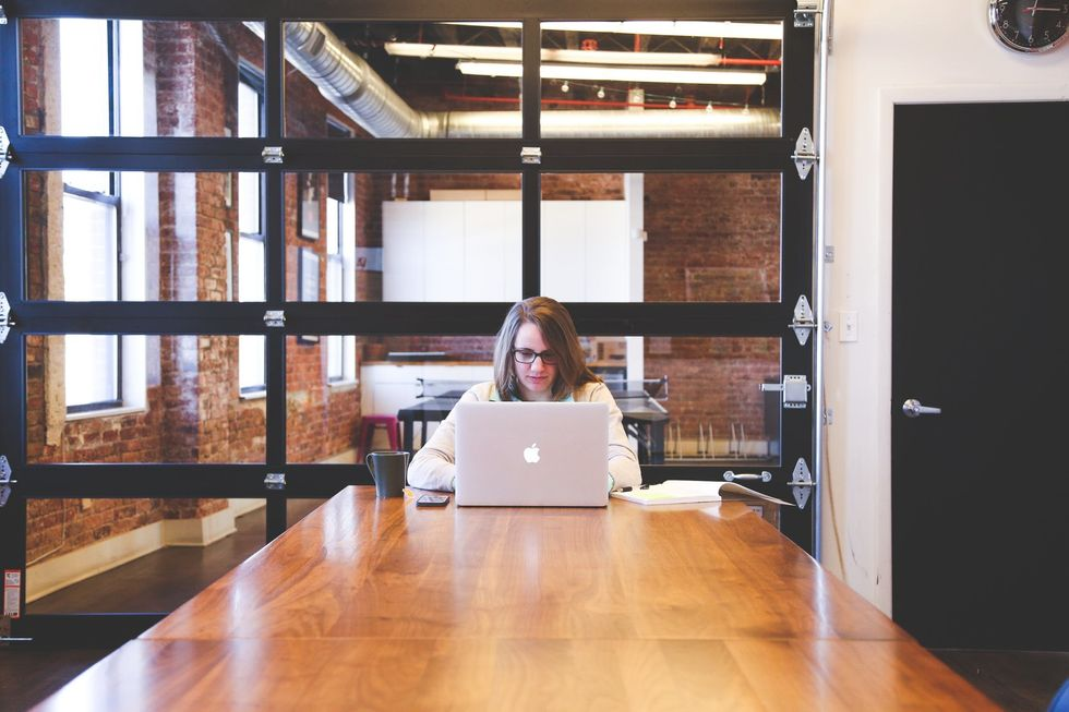 woman sitting at table working on laptop