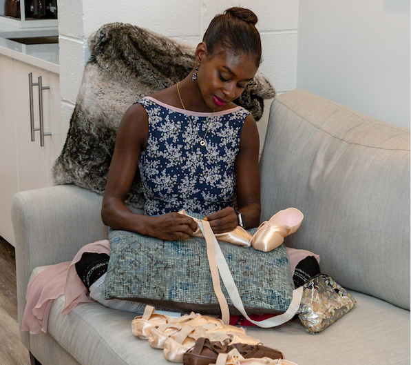 Ashley Murphy -Wilson sews her point shoes, sitting on a coach with several pairs in front of her