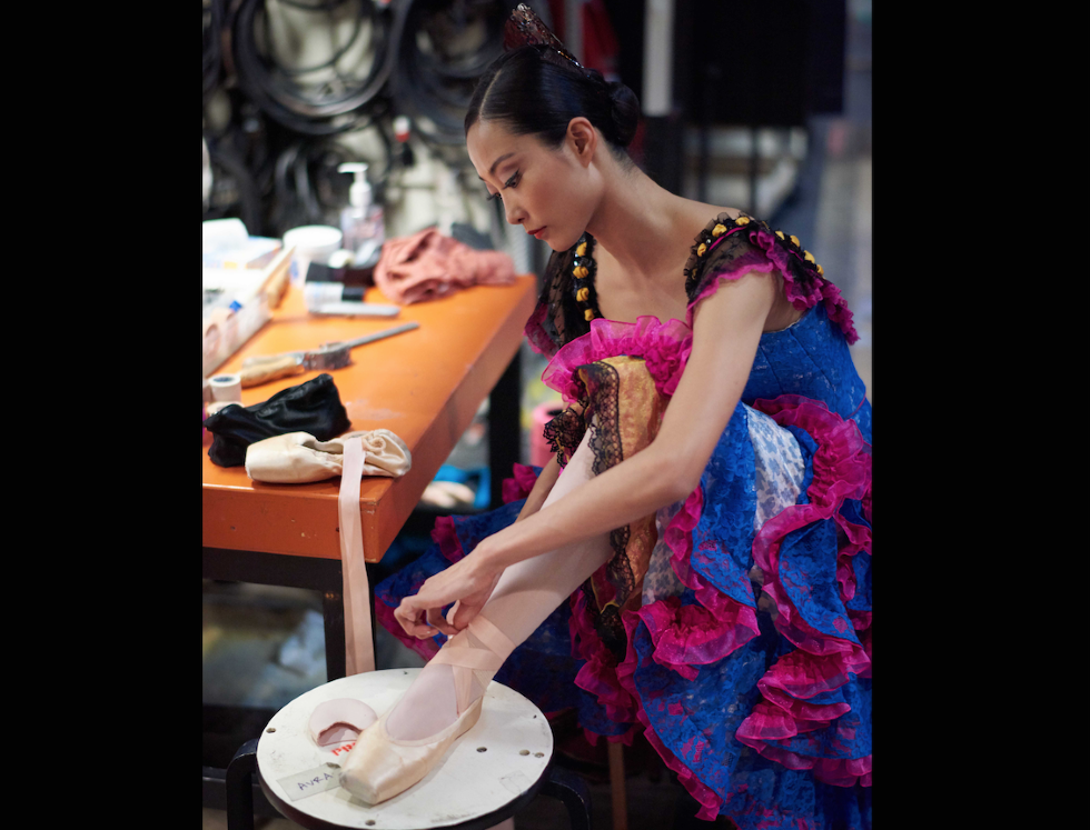WanTing Zhao ties her pointe shoes on a stool backstage