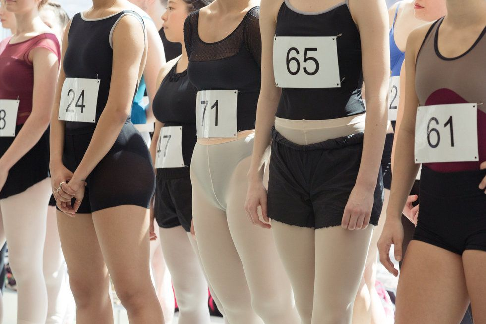 Auditioning dancers, wearing leotards and audition numbers pinned on to their clothing, are photographed from the shoulders down.