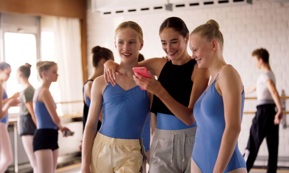 Lara stands with two friends in the ballet studio, looking at something on a phone. The friend in the middle has her arm around Lara.