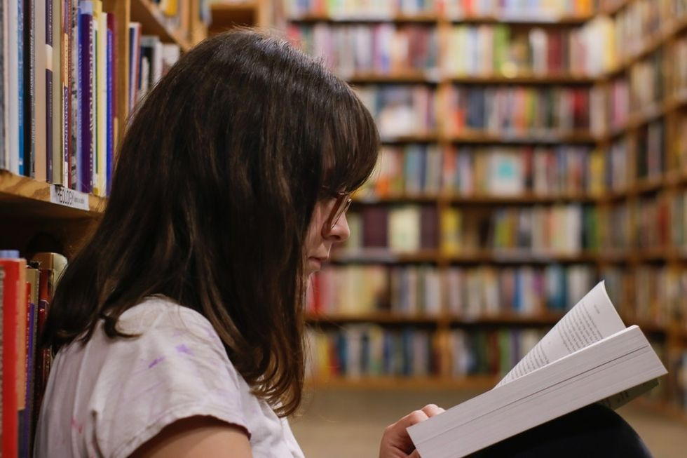 woman with glasses reading book in library