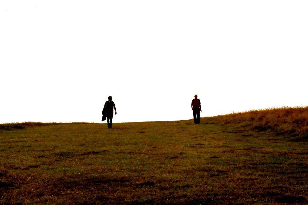 Two people walking up a hill of some kind