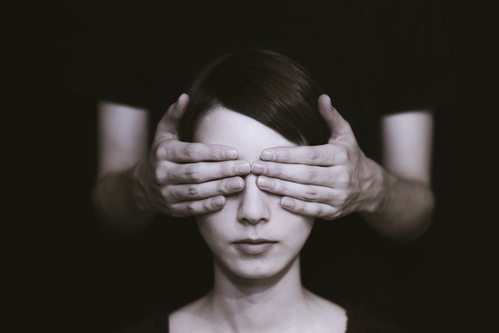 Woman with her eyes being covered by someone else's hands.