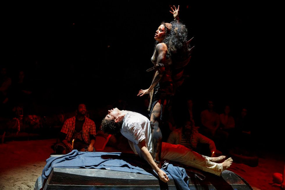 A man lies on a bed, his chest arched up as if being summoned by the woman standing above him. She has paint on her body and disheveled hair and motions as if she is cursing him. The audience can be seen dimly in the background.