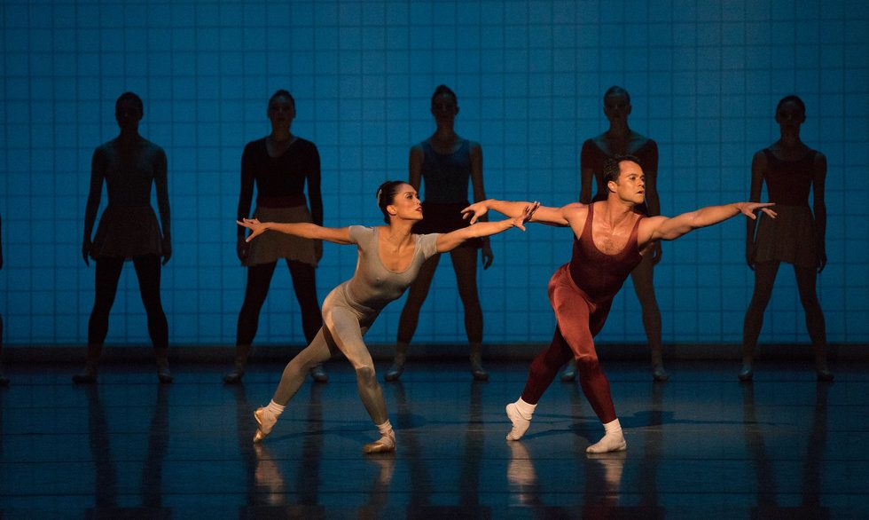Cirio (in a gray unitard) and Arrais (in a red unitard) are both in deep lunges. Five dancers stand, facing front, in the background.
