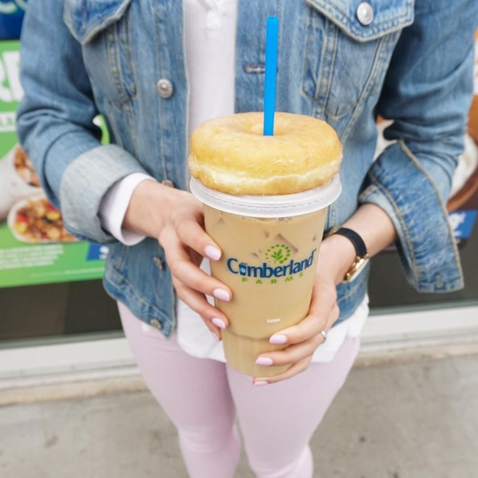 woman in denim jacket holding cumberland farms iced coffee
