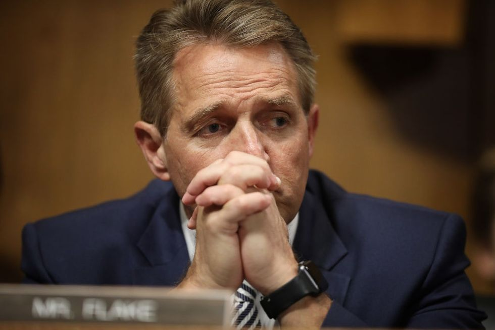 Jeff Flake refuses to look at two women who confront him in elevator after he announces support for Kavanaugh.