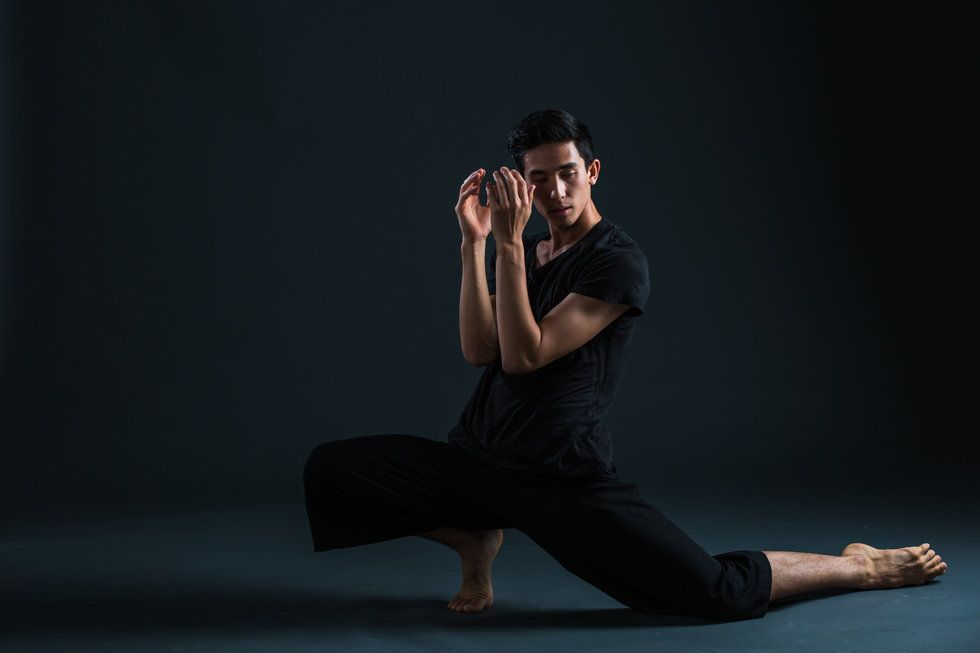 Obremski, wearing all black, poses against a dark background. His arms are in front of his face, and he is in a low, force-arch lunge.
