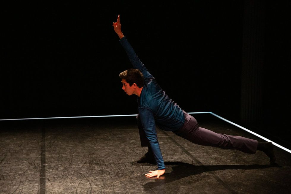 Obremski performs on a black stage with a black scrim. He is in a deep lunge, facing left, with his right arm in the air.