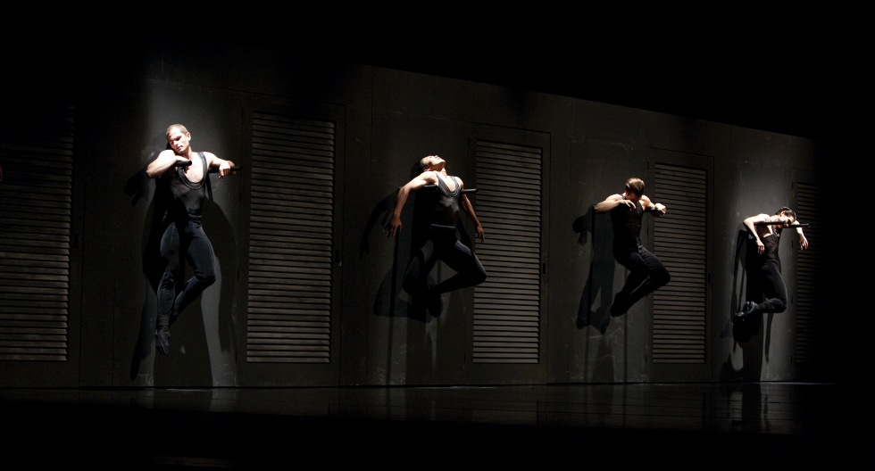 Four male dancers hang from a wall, all in black