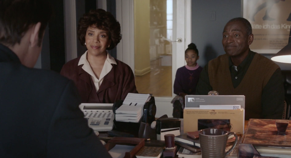 A screenshot from the show in which the ballet director talks to Beth and her parents in his office.