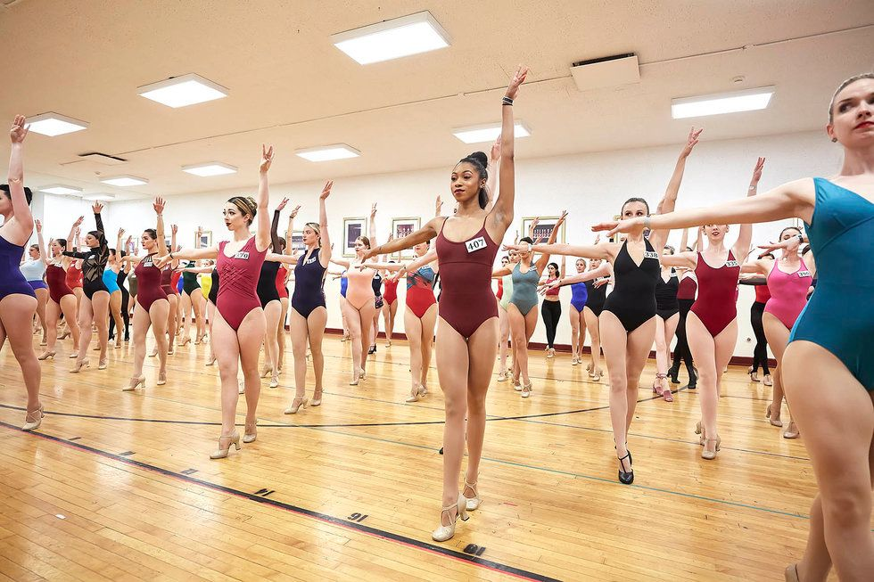 Women in leotards and tights with numbers pinned to their chests stand in a fourth position relev\u00e9, left arm reaching to the sky.