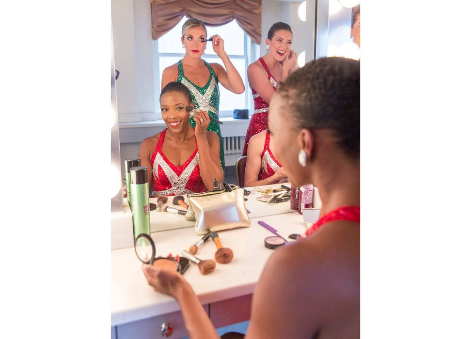 Three Rockettes do their makeup in the dressing room. Danelle Morgan is seated in the center, smiling as she applies blush