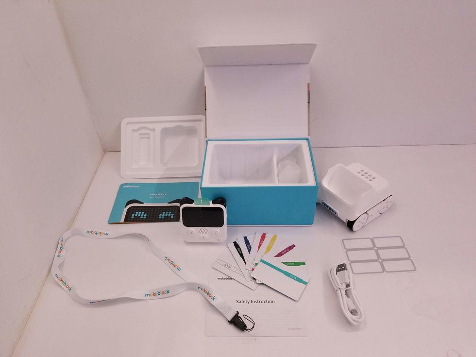 Une photo de tout ce qui se trouve dans la boîte Codey Rocky, y compris le contrôleur, le châssis, la carte couleur et un chargeur