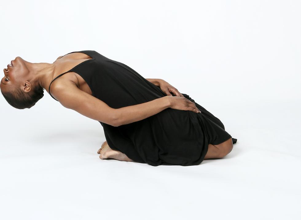 Okwui Okpokwasili on her knees leaning back