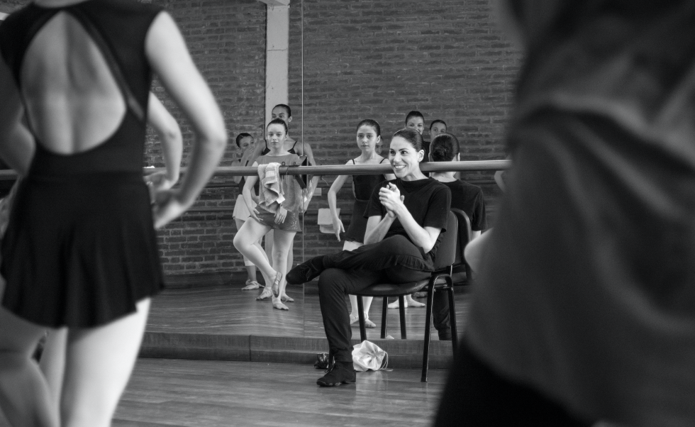 Paloma Herrera sits in a chair in from of a mirror in the ballet studio, smiling at students