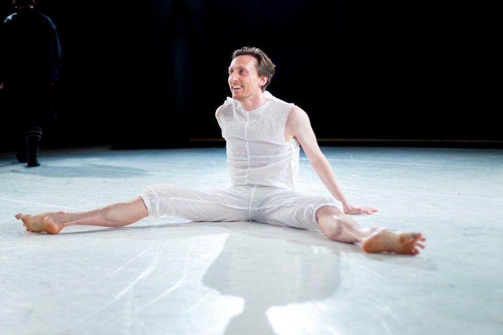 Reid Bartelme sits on the floor of the stage in costume, casually looking up and talking