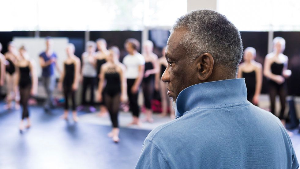 A closeup of Donald Byrd from behind, a row of dancers in the background