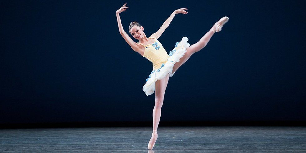 Arja onstage in a classical tutu, her right leg extended as she leans away from it.