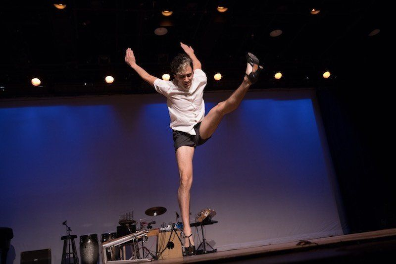 Teicher wearing high-heeled tap shoes, short black shorts and white button-down, jumping slightly off the ground with one leg extended in front of him and his arms reaching behind him.