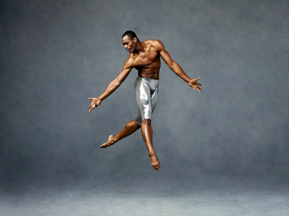 A photo from a photoshoot of Roberts jumping in the air, his legs crossed and his arms reaching towards the ground. He wears metallic shorts and looks toward his right hand.
