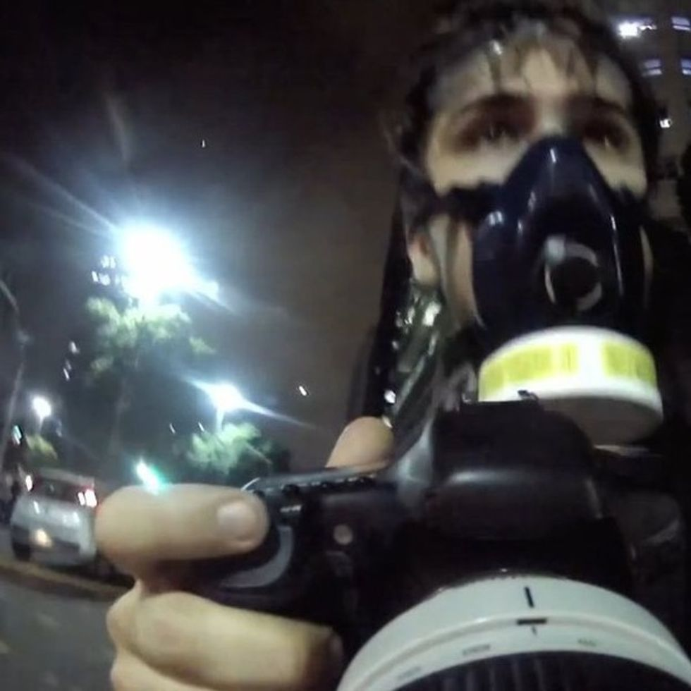 They shoot rubber bullets. He shoots powerful photographs.