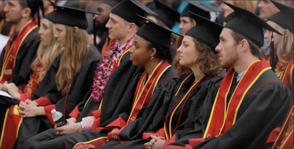 A row of students in cap and gowns listen to a graduation speech