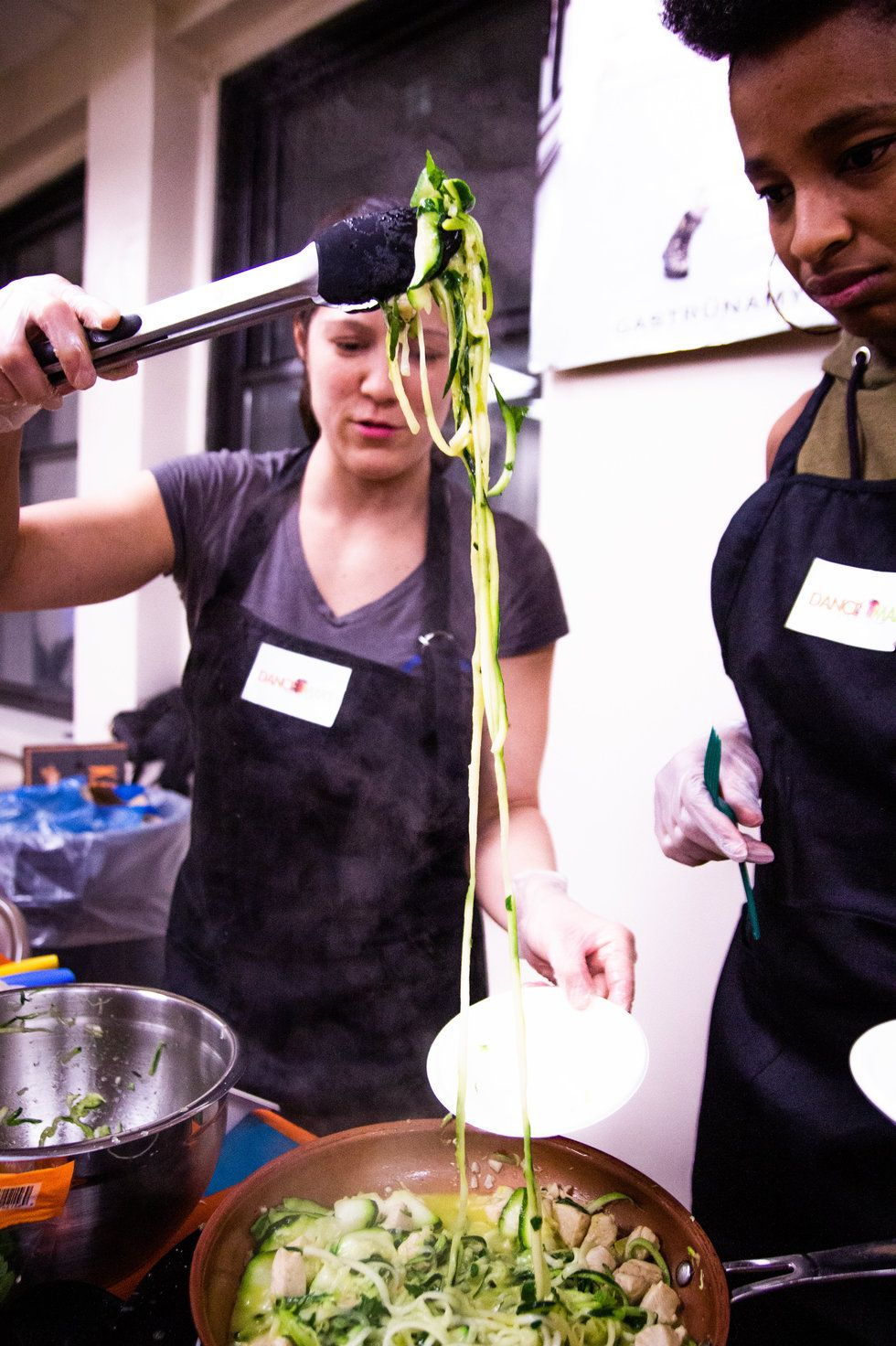 Two women stand over a pan of zucchini noodles and chicken, one uses a utencil to put some on a plate.
