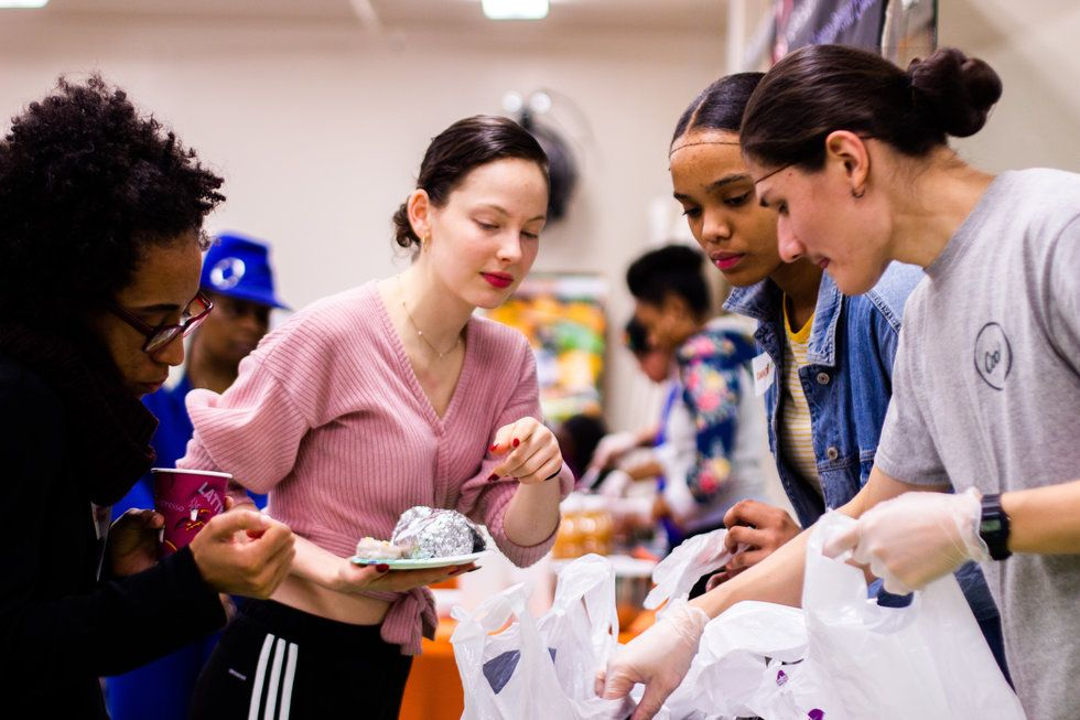 Four young women stand over bags of groceries, chatting